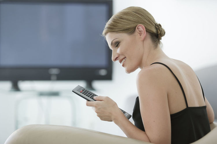 Smiling Woman Using Television Remote At Home