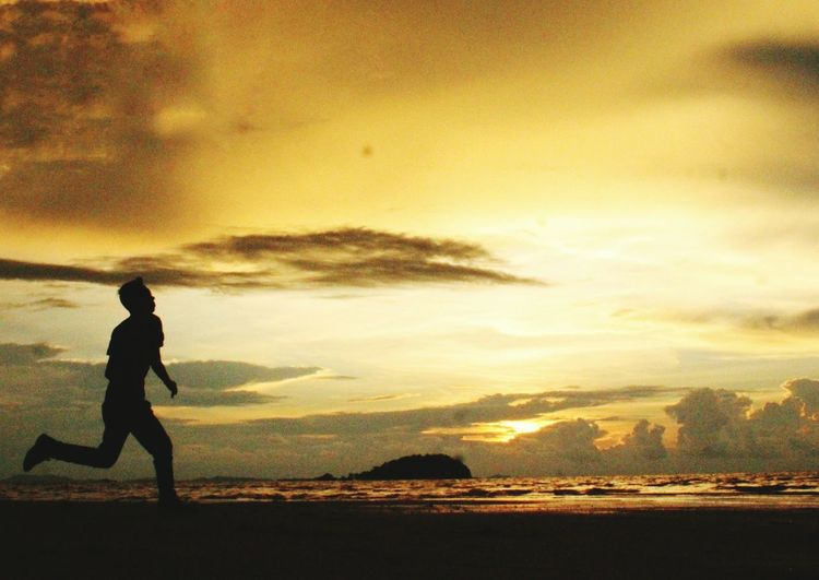 Silhouette boy playing on beach against sky during sunset