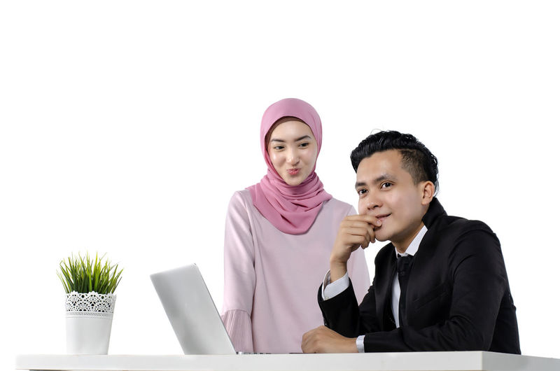 portrait of young couple entrepreneurs discussing ideas with a laptop in front of them Business Two People Front View Indoors  Waist Up Men White Background Adult Laptop Office Studio Shot Smiling Occupation Males  Young Adult Portrait Businessman Business Person Looking At Camera People Using Laptop
