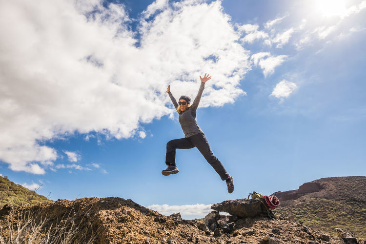 Low angle view of woman jumping on land against sky