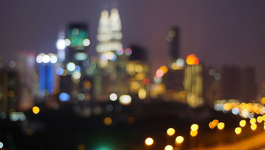 Malaysia city skyline illuminated at night.Blurry photo light and bokeh. Architecture Building Building Exterior Built Structure City City Life Cityscape Defocused Glowing Illuminated Lens Flare Light Multi Colored Night No People Office Building Exterior Outdoors Skyscraper Street Transportation Travel Destinations Vehicle Light