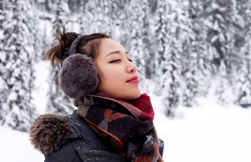 Woman With Eyes Closed On Snow Covered Field During Winter