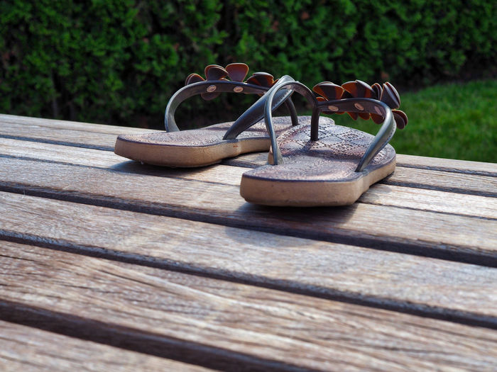 Close-up of shoes on wooden table