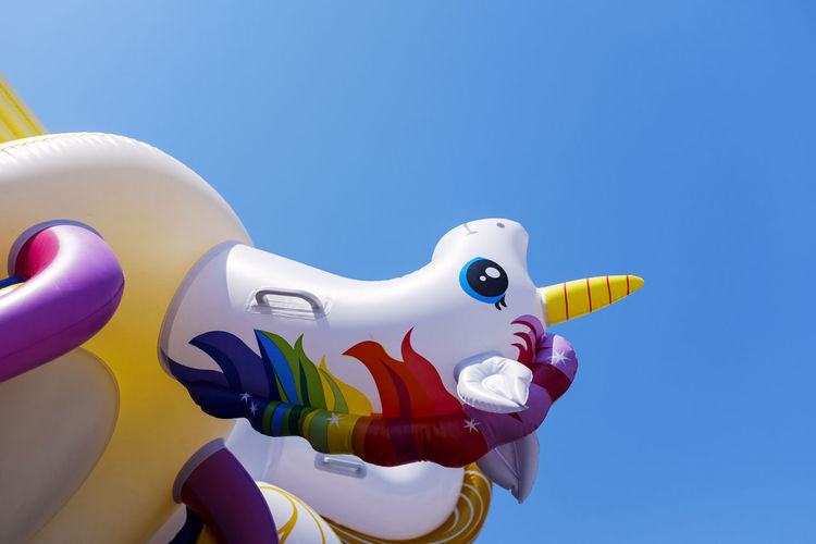 Low angle view of stuffed toy against clear blue sky