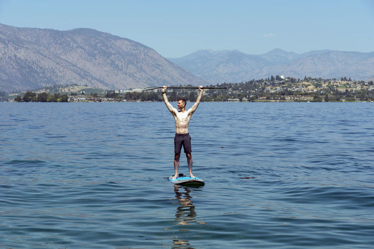 Man exercising on stand up paddle board with arms overhead. Arms Raised Beauty In Nature Day Holiday Human Arm Leisure Activity Lifestyles Limb Mountain Mountain Range Nature One Person Outdoors Real People Scenics - Nature Sky Trip Vacations Water Waterfront