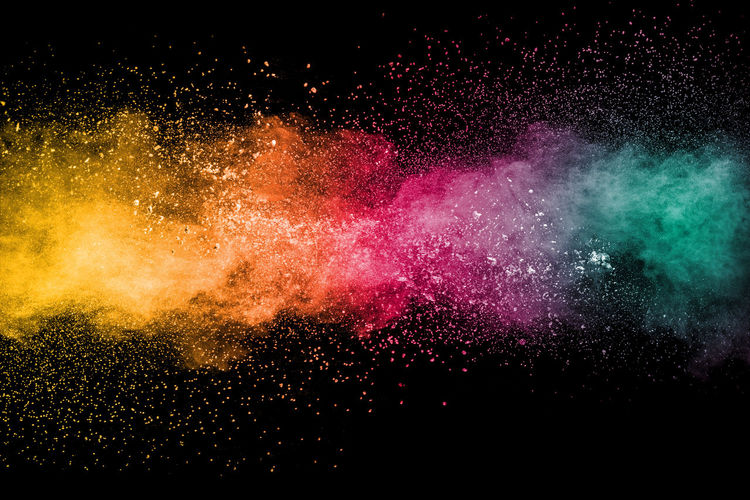 Close-up of powder paint splattering against black background