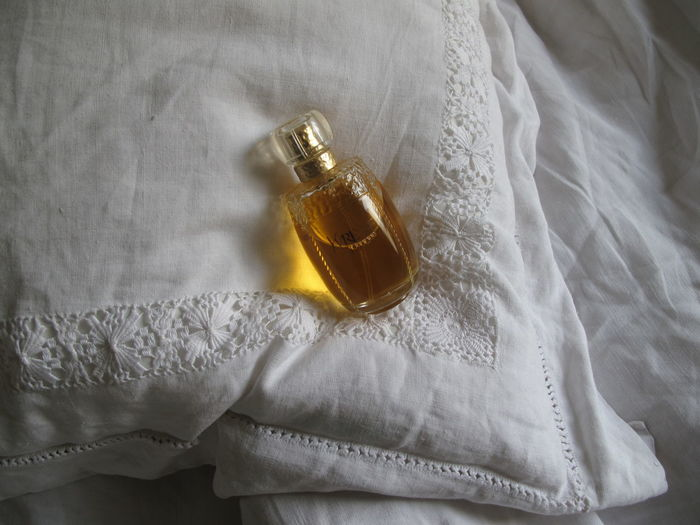 High angle view of perfume bottle on bed at home
