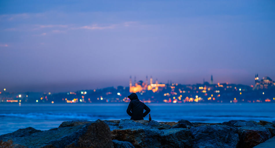 Lonely man enjoying view against the backdrop of the old city. Bokeh City City Life Cityscapes Dusk Lifestyles Men Blue Wave Natanomalous.com Nature Fine Art Photography The OO Mission 43 Golden MomentsNature_collection Night Rear View Landscapes With WhiteWall Sea Sea And Sky Sihouette  Color Palette Colour Of Life Two Is Better Than One Cities At The Night My Year My View The City Light Capture Tomorrow Moments Of Happiness It's About The Journey