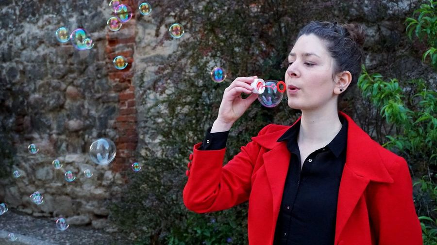 Young woman blowing bubbles against wall