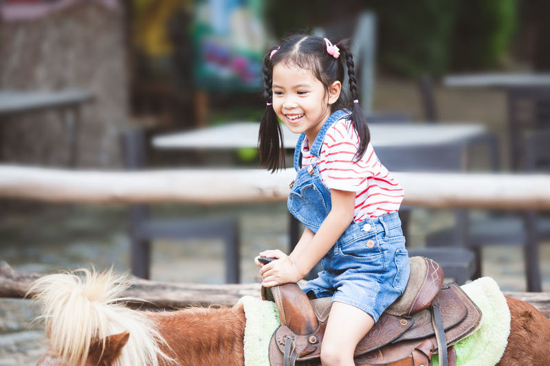 Cute asian child girl riding a pony in the farm with fun Asian  Farm Field Fun Horses Pony Recreation  Travel Trip Animal Child Domestic Animals Enjoy Girl Horse Horseback Jockey Kid Mammal Pets Play Riding Smiling