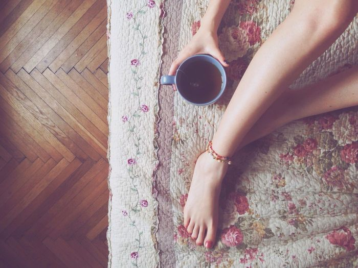 High angle view of woman with black tea sitting on rug at home