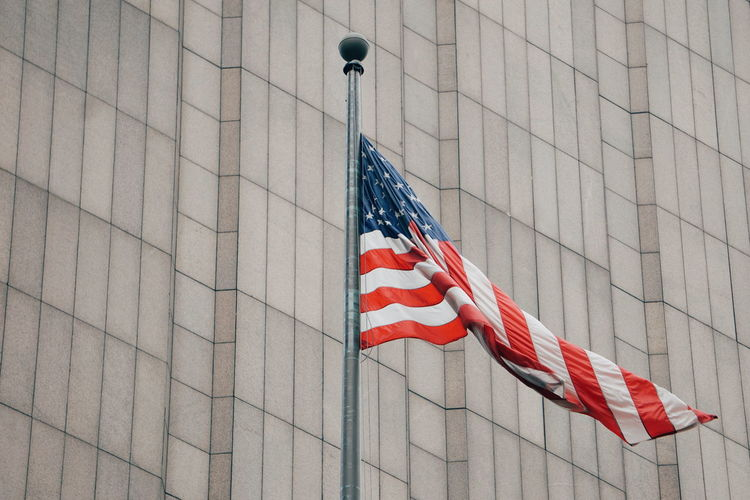 Low Angle View Of American Flag Against Building In City
