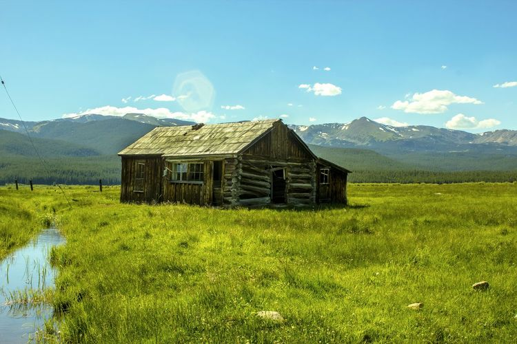 Wooden Rustic House On Grassy Field Against Distant Mountains