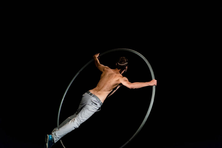 Circus Acrobat Agility Arts Culture And Entertainment Balance Black Background Circle Copy Space Dancing Flexibility Full Length Hairstyle Holding Indoors  Motion One Person Performance Plastic Hoop Skill  Strength Studio Shot Vitality Young Adult
