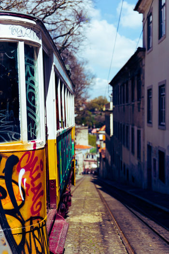 Painted Tram On Railroad Tracks In City By Buildings