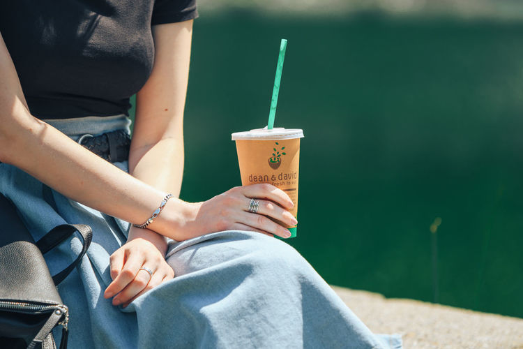 Midsection of woman holding drink while sitting outdoors