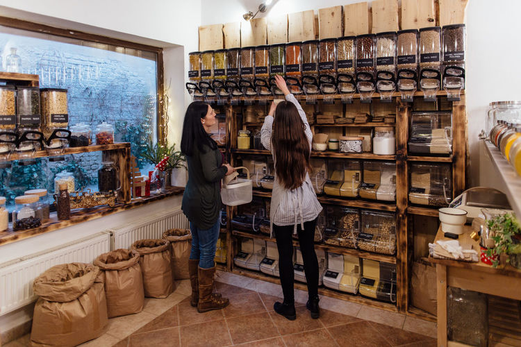 Shop assistant helping customer in packaging free shop. Zero waste shopping - woman buying fresh produce at package free grocery store. Zero Waste Plastic Free Package Shop Store Raw Food Food Refill Organic Shopping Business Homemade Horizontal Grocery Bulk Interior Container Dispenser Customer  Assistant Shopkeeper Two People Bio Eco