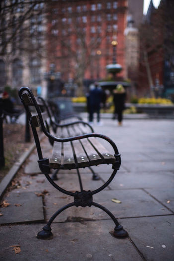 Empty bench on footpath by street in city