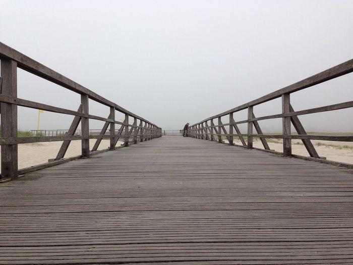Boardwalk On Beach Against Clear Sky