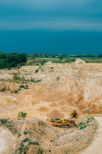 Minerals Construction Industry Construction Machinery Day Digging Environment Geology Industrial Equipment Industry Land Land Vehicle Landscape Machinery Mine Mining Mode Of Transportation Outdoors Plant Quarry Sky Stone Surface Mine Transportation Truck Vehicle