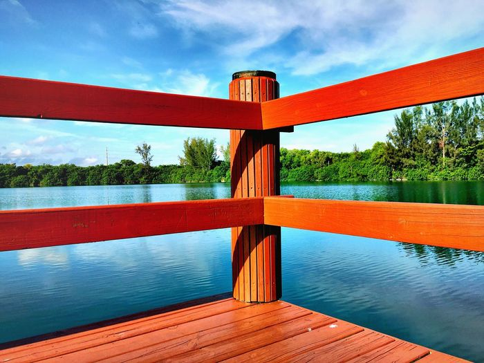 Red pier on lake against sky