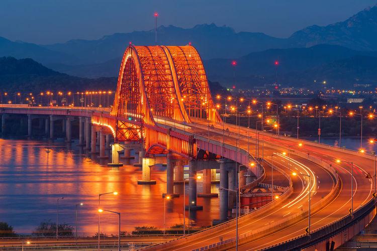 Illuminated banghwa bridge over han river at dusk