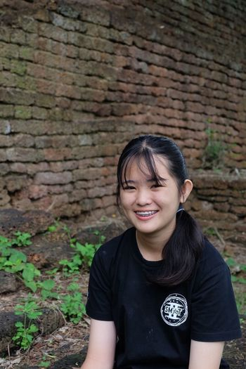 Portrait of young woman with braces smiling against brick wall