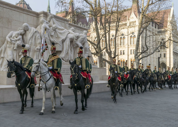 Hussars on horses in front of the Parliament House during the 15 March parade in Budapest, Hungary. Hussar cavalry lineup in traditional festive uniform. 15 March Budapest Holiday Horses Hungary National Rider Travel Uniform Architecture Cavalry Colorful Day Festive History Horseback House Hungarian Hussars Outdoors Parade Parliament People Riding Traditional