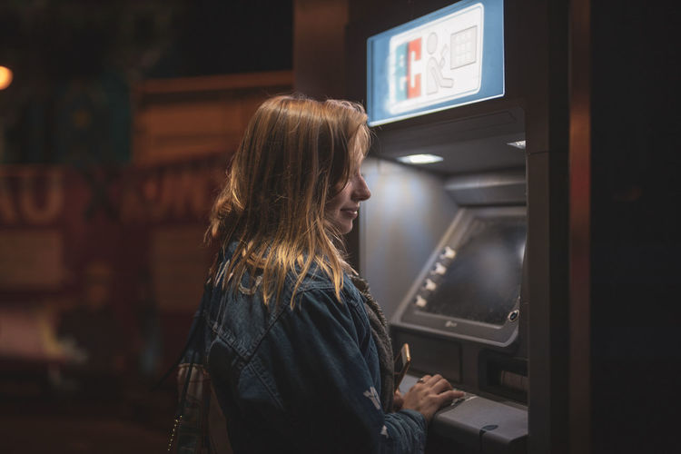 Side view of smiling young woman using atm at night