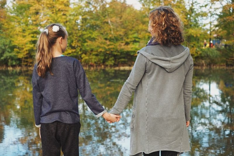 Mother and daughter enjoying the autumn Two People Togetherness Casual Clothing Person Leisure Activity Water Adult Outdoors Young Women Friendship Horizontal Happiness Young Adult City Bonding People Couple Day Reflection Hands Happy Love Real People Authentic Moments