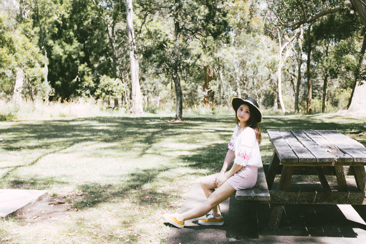 Full length portrait of mid adult woman sitting on picnic table in park