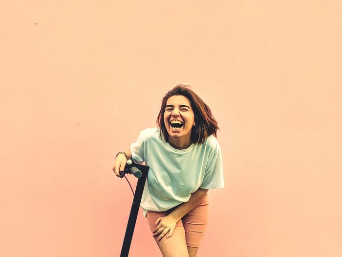 Cheerful young woman laughing against coral wall