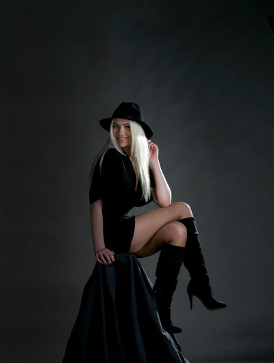 Portrait of woman wearing hat standing against black background