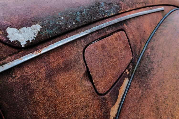 Close-up of old abandoned car gas tank lid