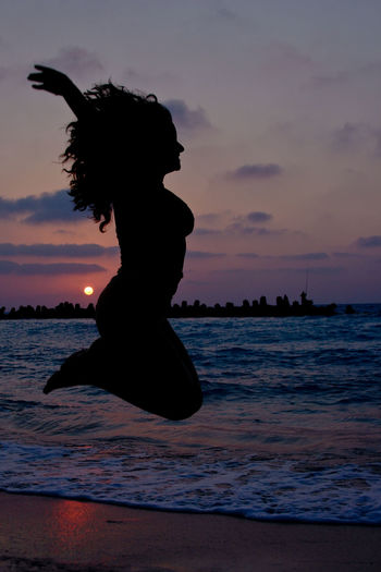 Silhouette woman jumping on shore at beach against sky during sunset