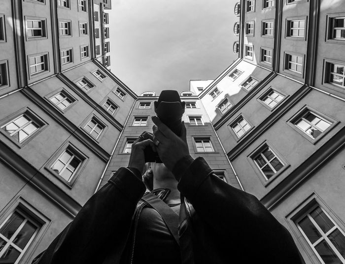 Low angle view of woman photographing against building in city