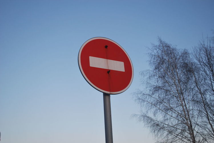 Low angle view of do not enter sign against clear sky