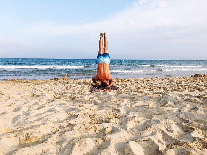 Rear view of shirtless man doing handstand on sandy beach