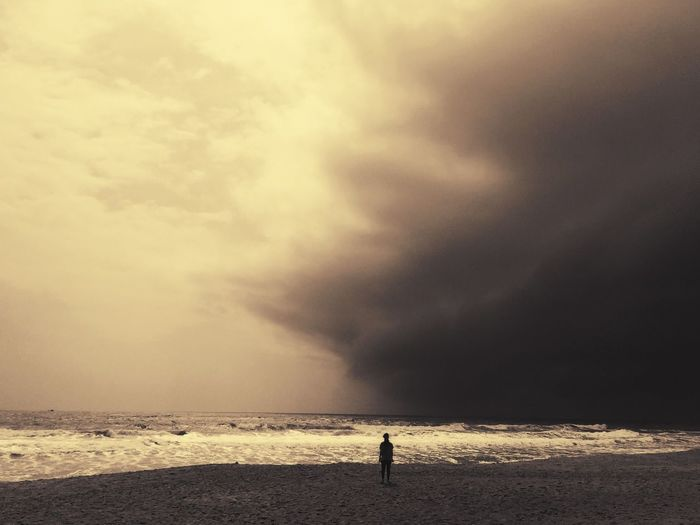 Person standing at beach against sky