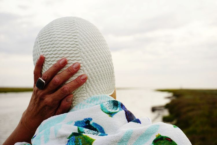 Rear view of woman wearing swimming cap standing at beach against sky