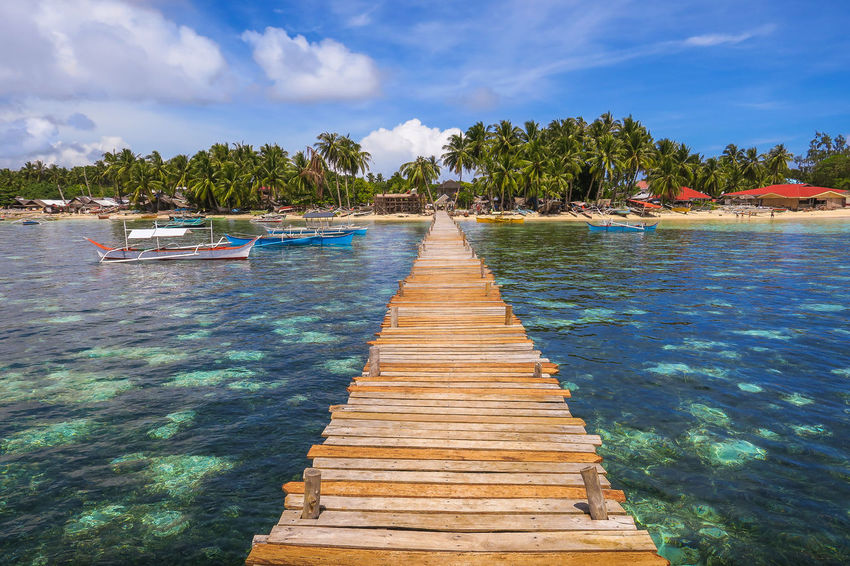 Wooden dock with planks stretching to island village Bliss Community Exotic Fishing Community Fishing Village Heaven Heaven On Earth Idyllic Island Island Beach Island Hopping Island Life Island Paradise Island Vibes Island View  Paradise Paradise Beach Paradise On Earth Shangri-La Shangrila Siargao Small Town Village Life Village View Wonderland