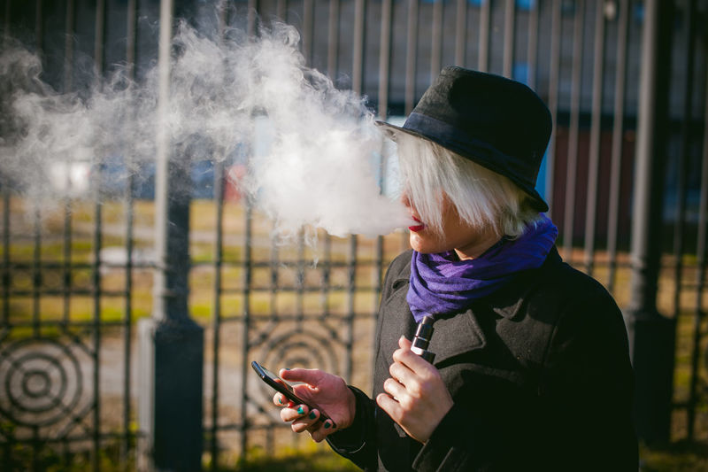 Young Woman Using Mobile Phone While Smoking At Park