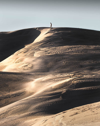 Distant view of man on sand dune in desert against sky