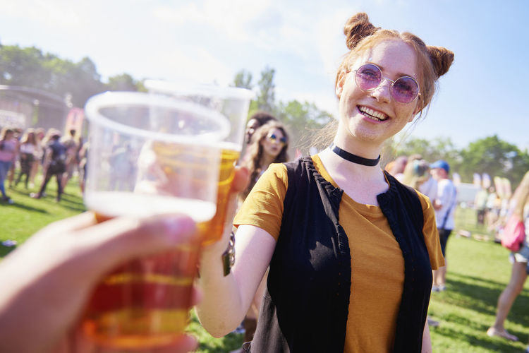 Cheerful young woman enjoying drink in party