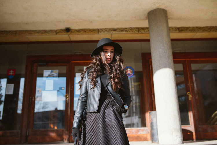 Young woman with long hair wearing jacket against closed glass door