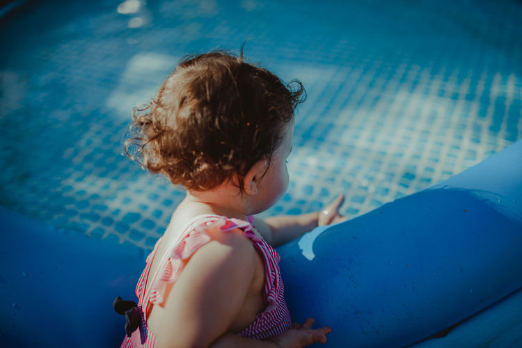 Side view of baby girl by wading pool