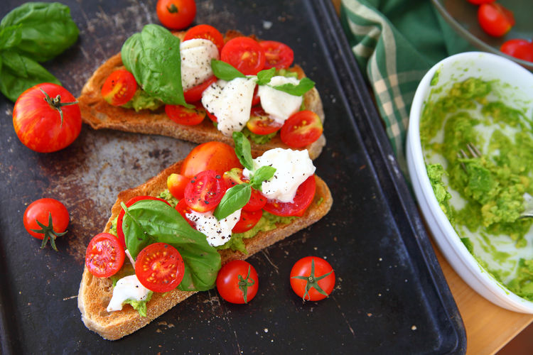 Avocado toast with burrata and tomatoes Food Healthy Eating Freshness Ready-to-eat No People Cherry Tomato Serving Size Green Color Snack Bread Avocado Toast  Caprese Fresh Basil Burrata Cheese Black Pepper Food Preparation Baking Pan Dishcloth Dishes Fresh Produce Breakfast Lunch Mashed Avocad Natural Light Overhead