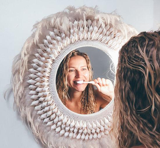 Reflection of beautiful woman brushing teeth seen through mirror