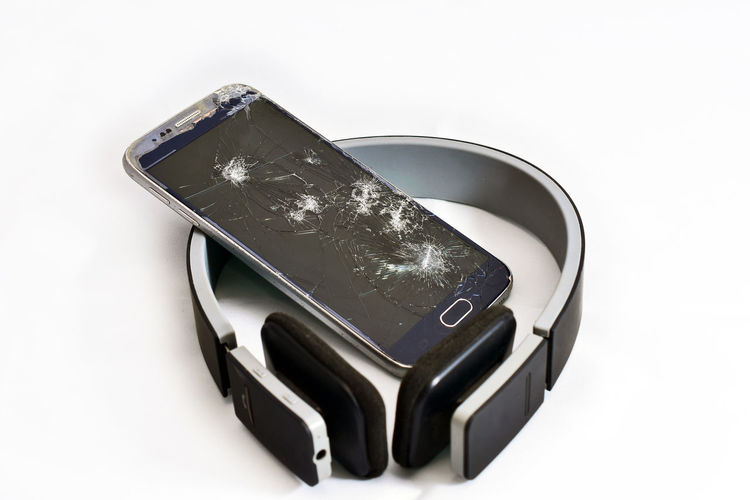 mobile phone with broken glass Headphone Communication Device Screen Destroyed Out Of Service Turned Off Unusable Without Communication White Background Studio Shot Film Industry Black Color Close-up