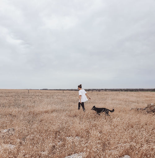 Woman walking with dog on field